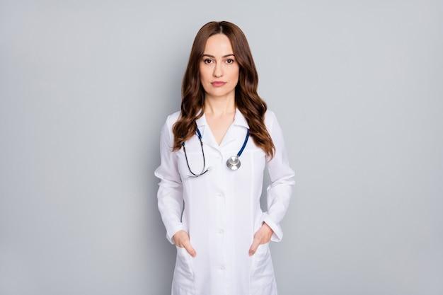 彼女の肖像画彼女は灰色のパステルカラーの背景の上に分離されたコート診断診断センターを身に着けている素敵な魅力的な経験豊富な熟練した薬用ウェーブヘアの看護師