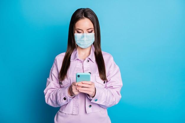 彼女の肖像画彼女はデバイス注文アプリショッピングウェブサービスを使用してガーゼの安全マスクを身に着けている素敵な魅力的な焦点を当てた女の子宅配孤立した明るい鮮やかな輝き鮮やかな青い色の背景
