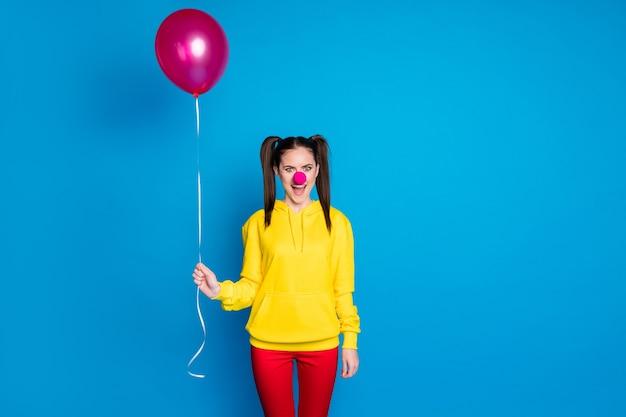 그녀의 초상화는 밝고 선명한 파란색 배경에서 격리된 재미있는 이벤트를 하는 헬륨 공을 손에 들고 있는 멋지고 재미있고 쾌활한 소녀 서커스 광대입니다.