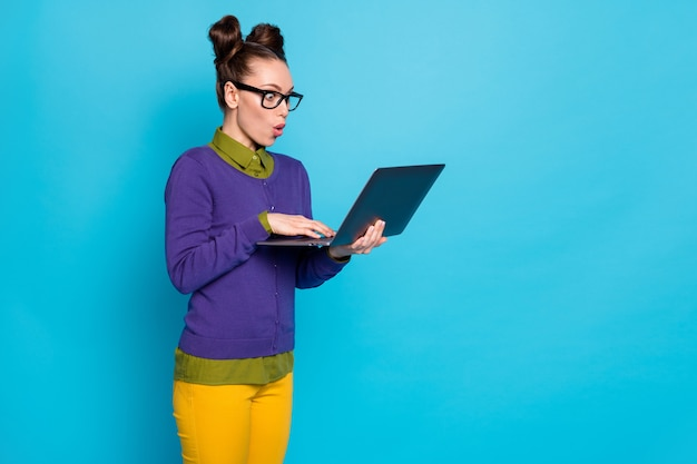 그녀의 초상화는 밝고 생생한 파란색 녹색 청록색 배경에서 격리된 웹 파트 타임 작업을 하는 노트북을 손에 들고 있는 멋지고 재미있는 유치하고 경쾌한 소녀입니다.