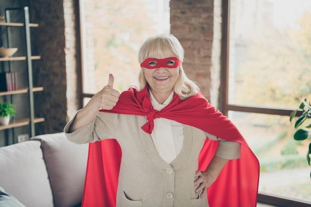 彼女の肖像彼女は素敵な魅力的な嬉しい陽気な陽気な白髪の女性が赤い衣装を着てスーパーおばあちゃんが工業用レンガ造りのロフトのモダンなスタイルのインテリアハウスでサムアップの優れたサービスを示しています