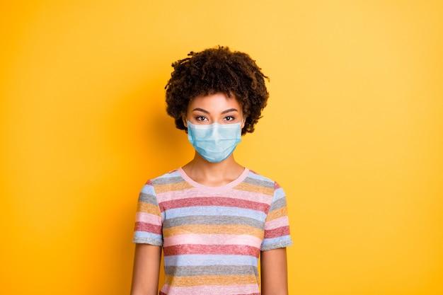 Портрет ее красивой привлекательной здоровой волнистой девушки в защитной марлевой маске, предотвращающей заражение гриппом и пандемией гриппа, изолированной на ярком ярком фоне яркого желтого цвета