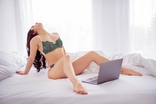 그녀의 초상화는 밝은 흰색 인테리어 하우스 아파트에서 놀리는 남자 친구와 노트북 채팅을 사용하여 침대에 앉아있는 그녀의 멋진 매력적인 사랑스러운 매혹적인 맞는 슬림 완벽한 누드 벗은 여자