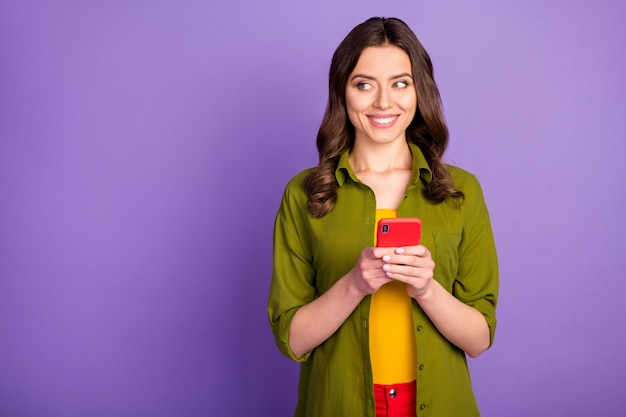 Портрет ее милая привлекательная очаровательная веселая девушка с волнистыми волосами, использующая сервис мобильных приложений, просматривающая веб-чат, изолированная на ярком ярком блеске, ярком лиловом фиолетовом фиолетовом цветном фоне