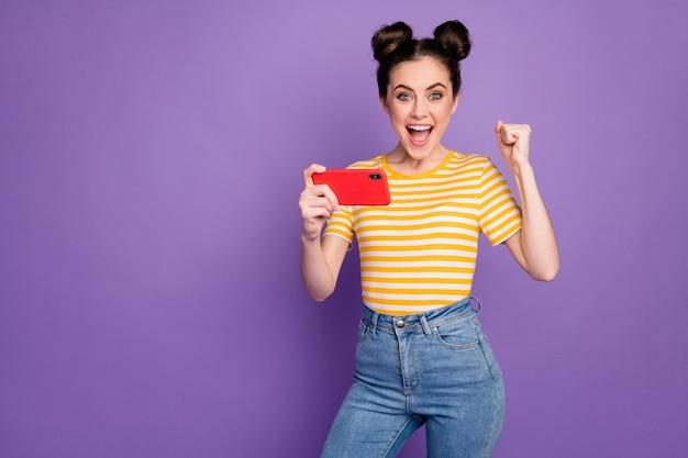 Портрет ее милая привлекательная милая веселая веселая девушка, фанатка, смотрящая по телевизору спортивный матч, развлекается, изолирована на ярком ярком блеске ярком лиловом фиолетовом фиолетовом цветном фоне