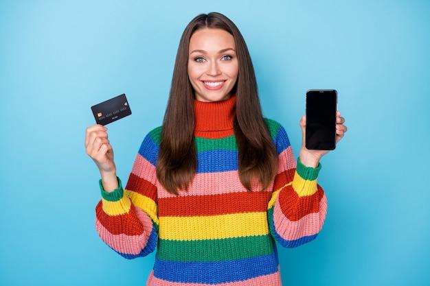 그녀의 초상화는 손에 있는 장치 은행 카드 클라이언트 서비스 전자 뱅킹 전자 지갑을 들고 있는 멋지고 사랑스럽고 쾌활한 소녀의 초상화는 밝고 생생한 선명한 파란색 배경에서 분리되어 있습니다.