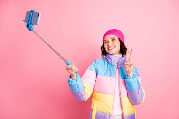 Портрет ее красивой привлекательной милой веселой веселой позитивной подруги, делающей селфи с v-образным знаком, изолированным на розовом пастельном фоне