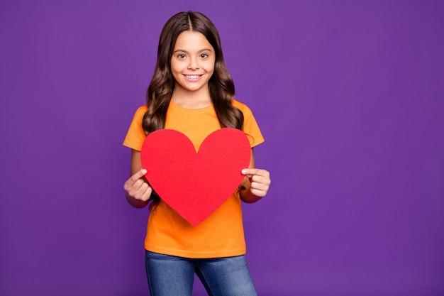 Портрет ее она милая привлекательная милая милая милая добрая веселая девушка с волнистыми волосами, держащая в руках большое большое сердце, изолированное на ярком ярком блеске ярком лиловом фиолетовом фиолетовом цветном фоне