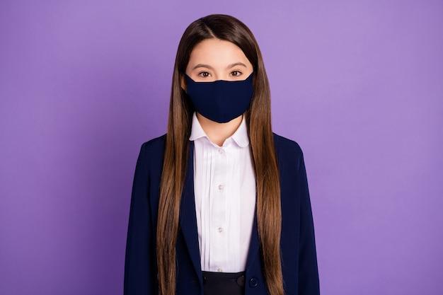 Портрет ее она милая привлекательная милая длинноволосая школьница прилежная ученица в текстильной хлопковой защитной многоразовой маске mers cov профилактика, изолированная на фиолетово-сиреневом фиолетовом цветном фоне