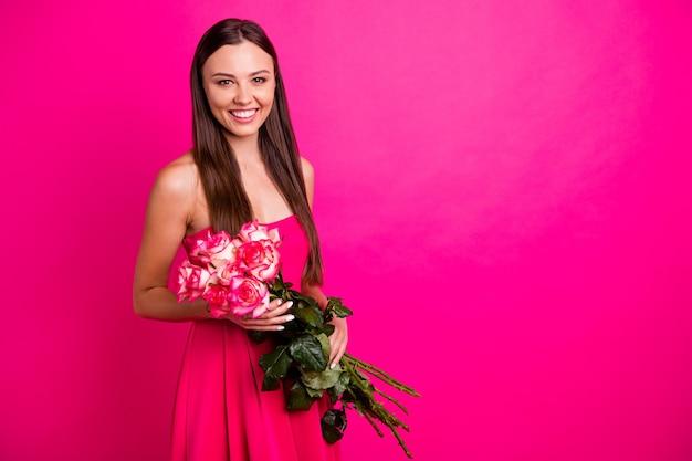Портрет ее красивой привлекательной милой веселой длинноволосой девушки, держащей в руках букет от парня, изолированного на ярком ярком сиянии яркого розового цвета фуксии