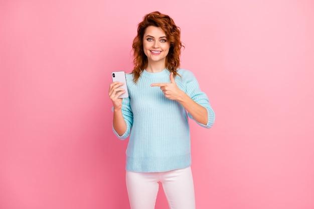 彼女の肖像画彼女の素敵な魅力的な素敵なかなり陽気な陽気なウェーブのかかった髪の少女は、ピンクのパステルカラーの背景の上に分離されたセルオンライン5gの新しいデバイスガジェットの最新技術を示しています