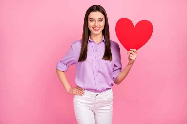 그녀의 초상화는 분홍색 파스텔 색상 배경에 격리된 큰 종이 심장을 손에 들고 있는 멋지고 사랑스럽고 멋지고 매력적인 쾌활한 장발 소녀의 초상화입니다.