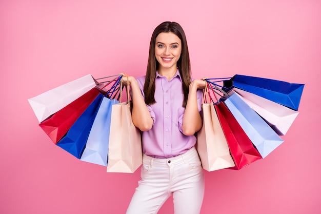 Портрет ее она милая привлекательная милая довольно модная веселая веселая длинноволосая девушка, держащая в руках покупки, тратящая деньги, изолированные на розовом фоне пастельных тонов
