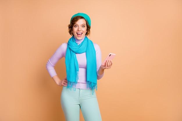 Портрет ее она милая привлекательная милая довольно рада взволнованная жизнерадостная веселая девушка, использующая просмотр ячеек smm обратная связь поделиться комментарием, изолированным на бежевом пастельном цветном фоне