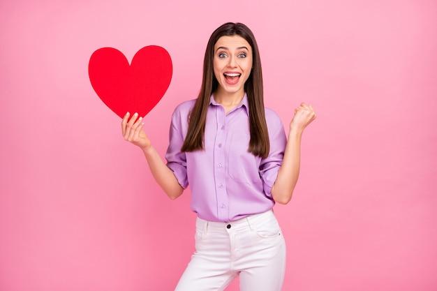 그녀의 초상화는 분홍색 파스텔 색상 배경에서 즐거운 시간을 보내는 큰 큰 종이 심장을 손에 들고 있는 멋지고 사랑스럽고 사랑스럽고 쾌활한 장발 소녀입니다.