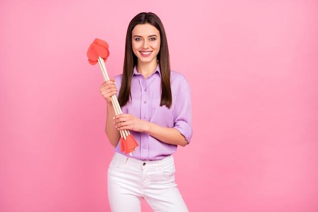 그녀의 초상화는 분홍색 파스텔 색상 배경에서 분리된 하트 화살을 손에 들고 있는 멋지고 사랑스러운 꽤 사랑스러운 달콤하고 쾌활한 장발 소녀의 초상화입니다.