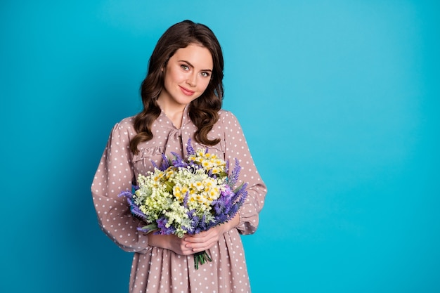 그녀의 초상화는 밝고 선명한 파란색 배경 위에 격리된 꽃송이를 손에 들고 있는 멋진 매력적인 사랑스럽고 쾌활한 여성스러운 물결 모양의 소녀입니다.