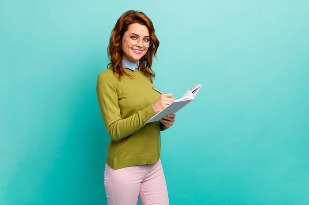 Портрет ее она милая, привлекательная, симпатичная, умная, умная, веселая, с волнистыми волосами, девушка, пишущая, готовит домашнее задание, изолированное на ярком ярком блеске, ярком бирюзовом фоне