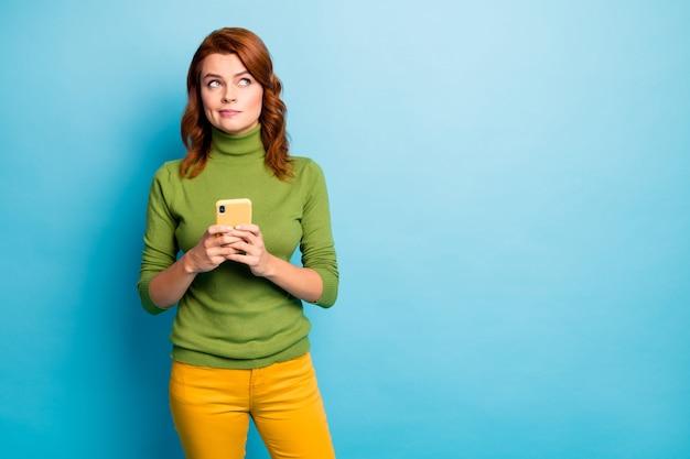 Портрет красивой привлекательной задумчивой волнистой девушки с волнистыми волосами, использующей сотовую связь, создавая новых подписчиков медиа-канала, изолированных на ярко-ярком сиянии яркой синей бирюзовой стене