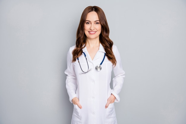 Портрет ее красивой привлекательной, довольно веселой, жизнерадостной, квалифицированной медсестры с волнистыми волосами, фонендоскоп, стетоскоп, изолированный на сером пастельном цветном фоне