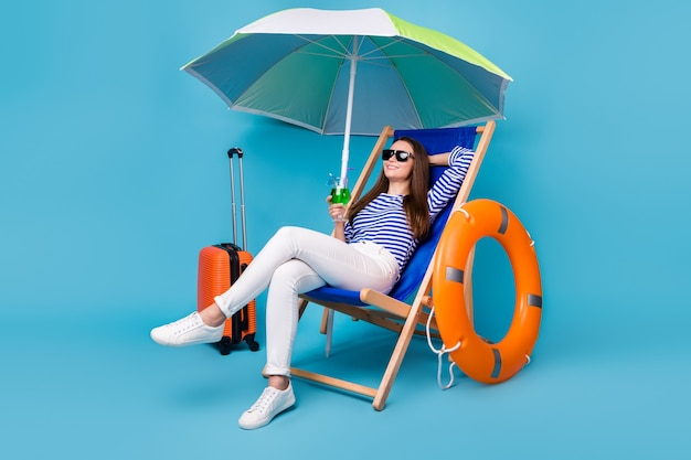 Портрет ее милая привлекательная довольно веселая девушка сидит в кресле, пьет напиток мохито, расслабляется, экзотический туризм, изолированный яркий яркий блеск, яркий синий цвет фона