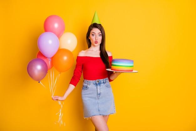그녀의 초상화는 맛있는 케이크 헬륨 볼을 손에 들고 있는 아주 멋지고 쾌활한 펑키한 여성스러운 소녀의 초상화입니다.