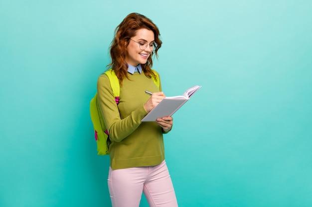 Портрет ее красивой привлекательной довольно творческой веселой веселой волнистой девушки, пишущей стратегию заметки для эссе, изолированной на ярком ярком блеске, ярком бирюзовом фоне