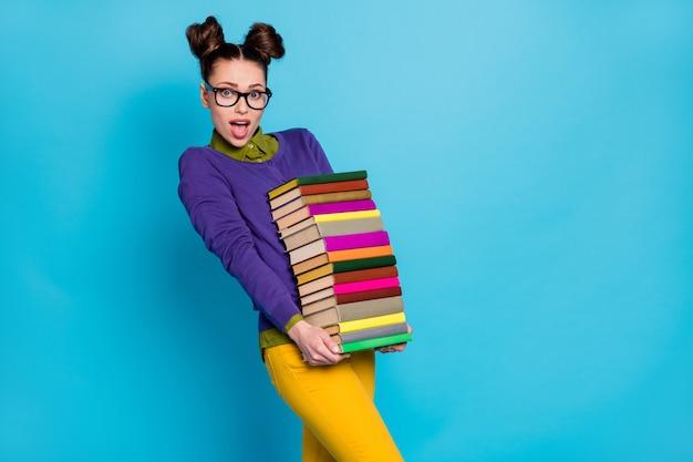 Портрет ее милая привлекательная довольно интеллектуальная прилежная ошеломленная девушка-компьютерщик, несущая большие тяжелые стопки книг, изолированные на ярко-ярком сияющем ярком сине-зеленом бирюзовом фоне