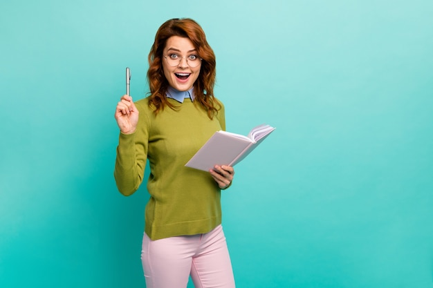 Портрет ее милая, привлекательная, умная, веселая, веселая, с волнистыми волосами, девушка пишет, готовит домашнее задание, создает сочинение, изолированное на ярком ярком блеске, ярком бирюзовом фоне