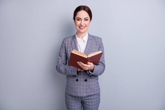 Портрет ее красивой привлекательной умной умной умной умной веселой учительницы в повседневном клетчатом костюме, читающей научную книгу, изолированную на сером пастельном цветном фоне