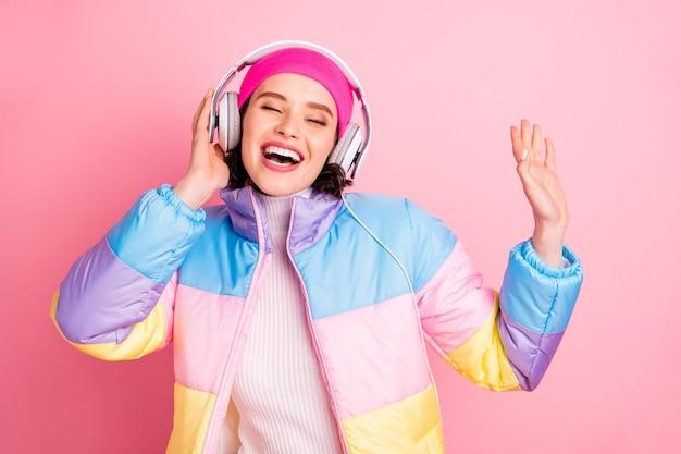 Портрет ее красивой привлекательной веселой веселой радостной девушки, наслаждающейся новым хобби аудиоплеера, изолированным на розовом пастельном фоне
