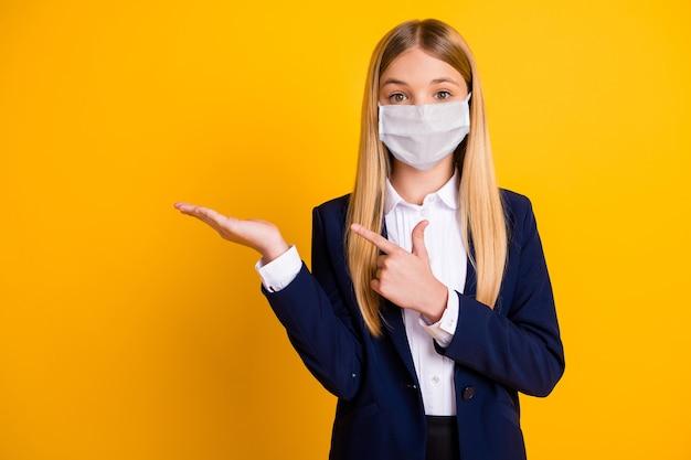 Портрет ее красивой красивой длинноволосой здоровой школьницы в защитной маске, показывающей, держащейся на ладони, копией пространства, совет mers cov, изолированный яркий яркий блеск, яркий желтый цвет фона