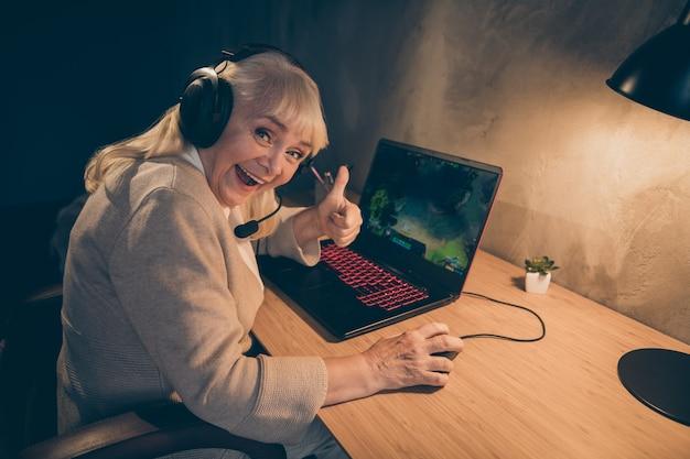 Портрет ее милая, веселая, седая блондинка, бабушка, играющая в игру, показывающая большой палец, совет, битва, чемпионат, победа в промышленном лофте, современный интерьер в бетонном стиле