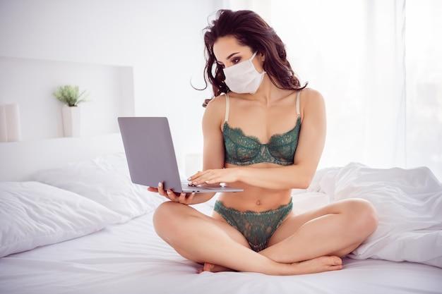 그녀의 초상화는 남자 친구 남편과 화상 채팅을 하는 거즈 마스크를 쓰고 침대에 앉아 있는 날씬하고 스포티하고 매력적인 사랑스러운 멋진 소녀의 초상화입니다. 밝은 흰색 인테리어 집 아파트
