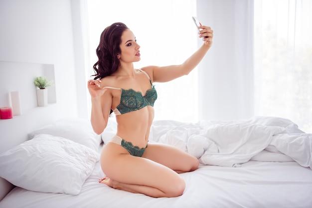 彼女の肖像画彼女は素敵なフィットスリムスポーティーなほっそりした魅力的な愛らしい女の子がベッドに座って自分撮りを作って写真を送る明るい白いインテリアハウスのアパートで夫のボーイフレンド