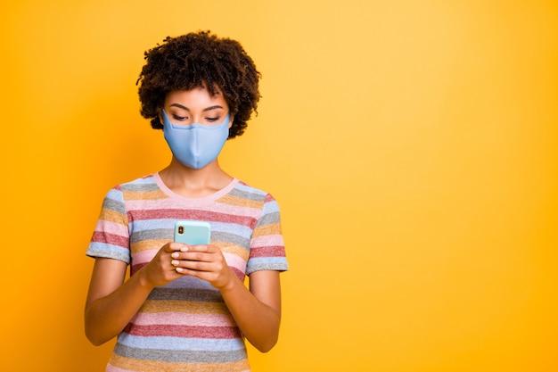 Портрет ее красивой сосредоточенной привлекательной волнистой девушки в защитной многоразовой маске с использованием устройства.