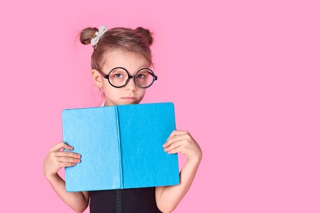 彼女の肖像画彼女は素敵なセクシーな素敵な魅力的な陽気な肯定的な学校の女の子がピンクの背景に分離された開いた本試験準備の後ろに隠れている手で保持しています。
