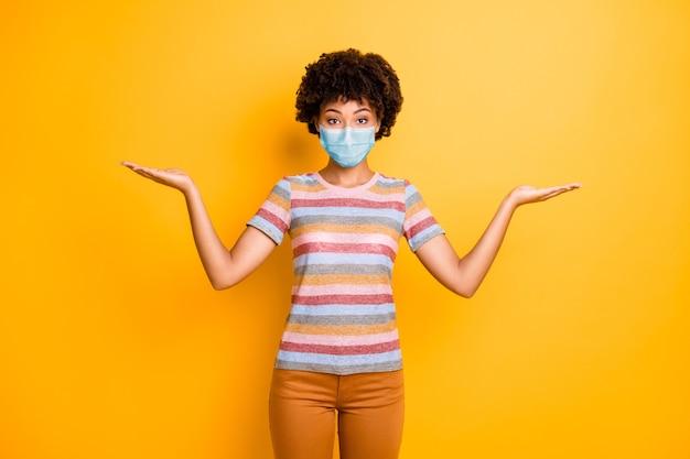 Портрет ее красивой здоровой волнистой девушки-медсестры в маске безопасности, держащей копию пространства на ладонях, концепция гриппа mers cov, изолированная ярким ярким блеском, ярким желтым цветом фона