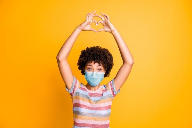 Портрет ее красивой здоровой волнистой девушки в марлевой маске, показывающей медицину в форме сердца, изолированную социальную дистанцию, яркий яркий блеск, яркий желтый цвет фона