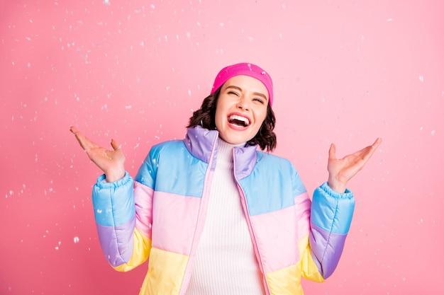 Портрет красивой привлекательной милой веселой, жизнерадостной, восторженной девушки, весело проводящей время, наслаждаясь падающим снегом, изолированным на розовом пастельном фоне