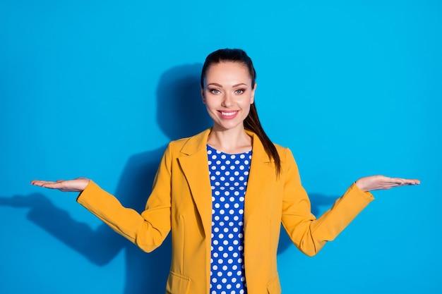 밝고 선명한 파란색 배경 위에 격리된 손바닥 복사 공간 광고 솔루션을 들고 있는 그녀의 잘 생긴 매력적인 매력적인 꽤 세련된 화려한 쾌활한 여성 리더의 초상화