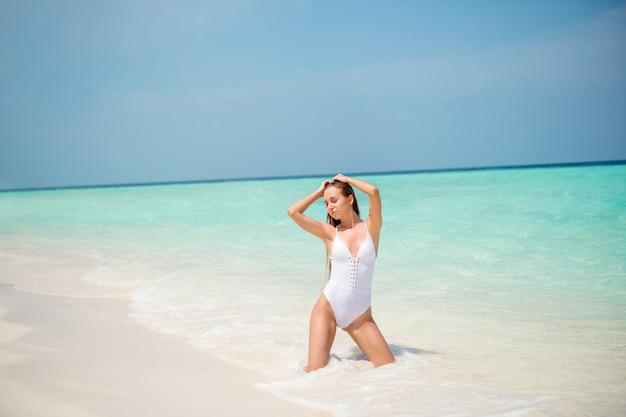 Портрет ее красивой привлекательной великолепной изящной девушки-модели, которая наслаждается летним отдыхом, проводя выходные, роскошный курортный отель, тур, позирует в солнечную погоду