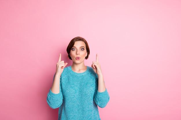 Портрет красивой, привлекательной, милой, веселой, испуганной, изумленной шатенки, указывая двумя указательными пальцами вверх