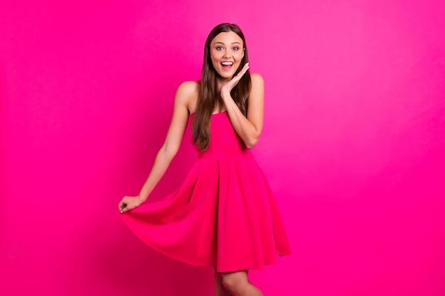 Портрет ее красивой привлекательной прекрасной великолепной жизнерадостной веселой изумленной длинноволосой девушки, выражающей восторг, изолированную на ярком ярком сияющем ярком розовом цветном фоне