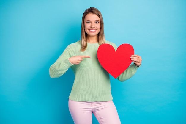 그녀의 잘 생긴 매력적인 사랑스럽고 쾌활한 쾌활한 소녀의 초상화는 회색 밝은 생생한 광택 생생한 파란색 배경에 고립 된 종이 심장을 보여주는 손을 잡고
