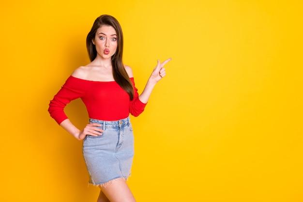 Портрет ее красивой привлекательной милой довольно великолепной изумленной девушки, показывающей копию пустого пустого места, рекламное объявление, надутые губы, изолированные на ярком ярком блеске на ярком желтом цветном фоне