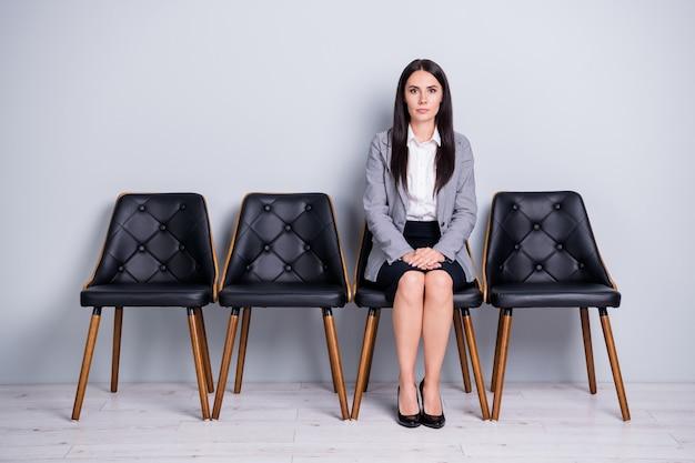 彼女の肖像画彼女は見栄えの良い魅力的なかなり上品な真面目な女性マーケター金融投資家の椅子に座ってプロモーション業界の孤立した明るいパステルグレーの色の背景を期待しています
