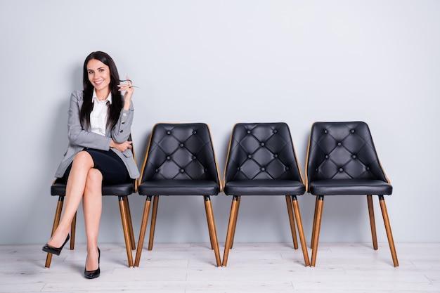 彼女の肖像画彼女は見栄えの良い魅力的なかなりエレガントな陽気な女性パートナーリーダーエコノミストマーケター椅子に座って孤立した明るいパステルグレーの色の背景に会うことを期待しています