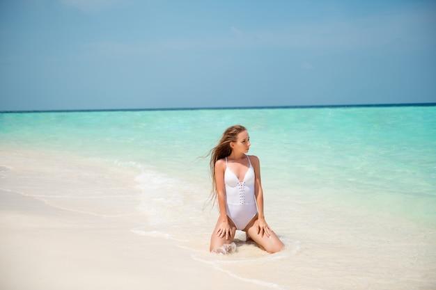 Портрет ее красивой привлекательной стройной длинноволосой девушки, наслаждающейся солнечным днем, хорошей погодой, приморским роскошным курортным спа-туром, туризмом, сидя на песке, чистой прозрачной воде