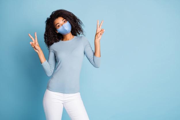 Портрет ее модной привлекательной подруги, показывающей двойной v-знак, копирующее пространство, стоп, заражение пандемией, грипп, профилактика гриппа, вирусная пневмония, изолированный синий пастельный цвет фона